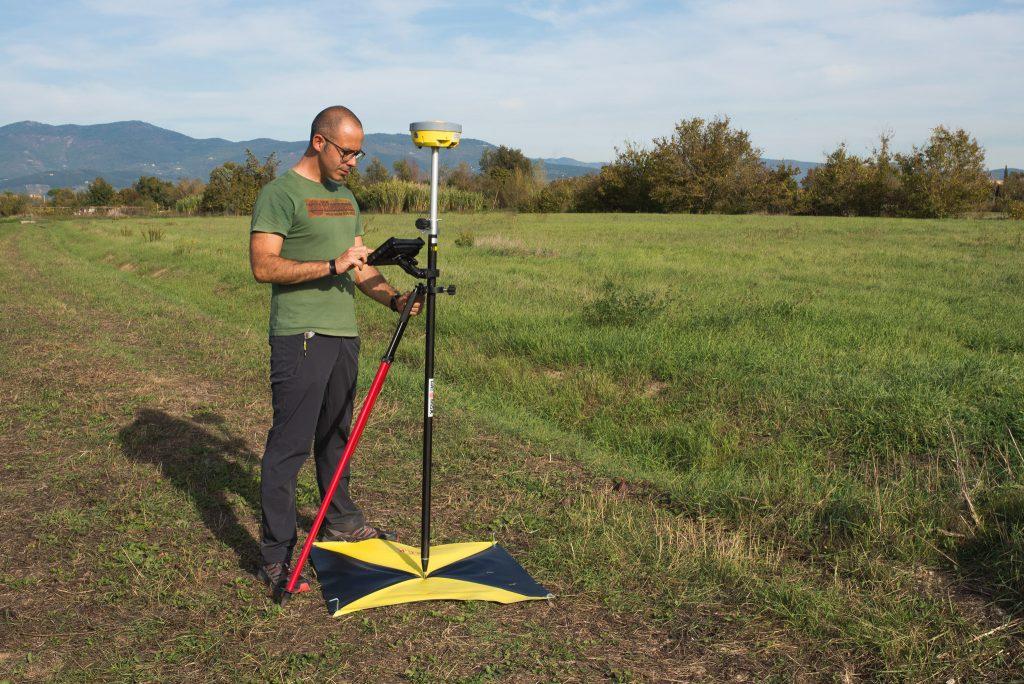 Fotografia di Paolo Corradeghini mentre rileva le coordinate di un target a terra con strumentazione GNSS