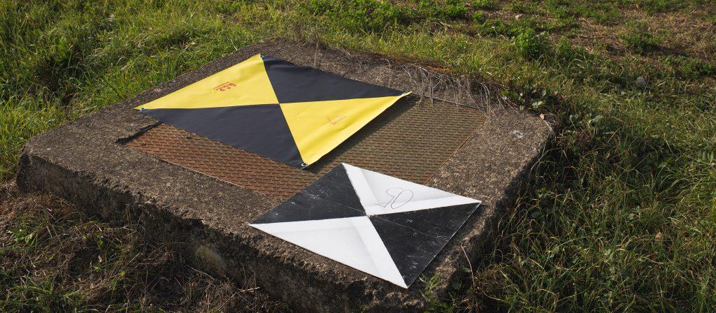 Fotografia di due target artificiali a terra, uno in PVC morbido 80x80 cm e l'altro in plastica rigida 60x60 cm